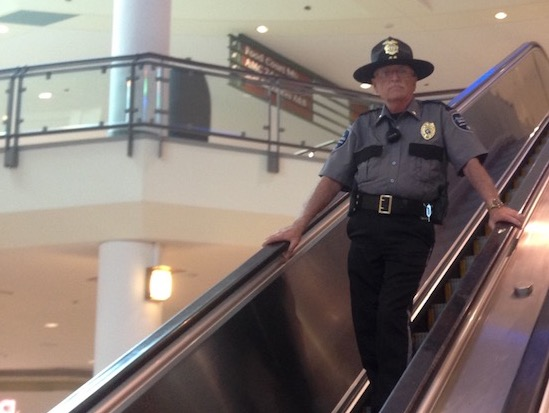 Security Officer Descending Mall Escalator